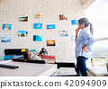 Hispanic Woman Working As Photographer Checking Images In Studio 42094909
