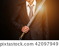The right hand of businessman holding sword  42097949