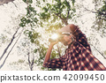 Young man looking through binocular in forest 42099450