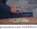 Mafia holding gun with ammunition and money 42099554