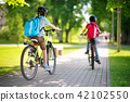 Children with rucksacks riding on bikes in the park near school 42102550