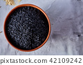 Black sesame seeds in a clay bowl on white textured background, close-up, top view. 42109242