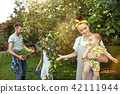The happy young family during picking apples in a garden outdoors 42111944