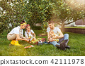 The happy young family during picking apples in a garden outdoors 42111978