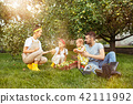 The happy young family during picking apples in a garden outdoors 42111992