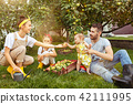 The happy young family during picking apples in a garden outdoors 42111995