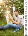 The happy young family during picking apples in a garden outdoors 42111997