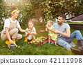 The happy young family during picking apples in a garden outdoors 42111998