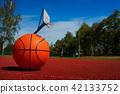Orange basketball against the blue cloudy sky 42133752