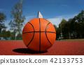 Orange basketball against the blue cloudy sky 42133753