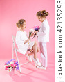 Twins girls in light clothes with bouquets of flowers posing near a chair on a pink background. 42135298