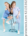Girls twins in light blue clothes are posing near a bar stool on a blue background. 42135302