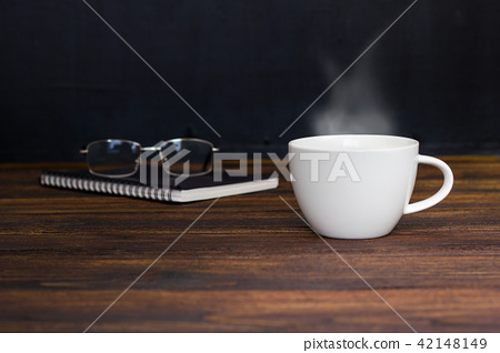 White coffee cup with smoke ,glasses and notebook. 42148149