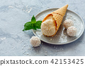 Ball of coconut ice cream in a waffle cone. 42153425