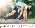 Muscular athlete preparing for race outdoors  42156573