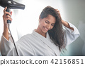 Happy lady drying hair with equipment 42156851
