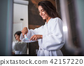 Positive lady brushing teeth in apartment 42157220