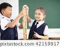 happy children playing wood blocks in classroom 42159917