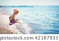 little boy walking at the beach in straw hat 42167933