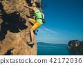 female rock climber climbing on seaside cliff 42172036
