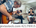 Repetition of rock music band. Electric guitar player and drummer behind the drum set. 42176915