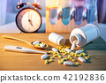 Pills spilling out of pill bottles on wooden table 42192836