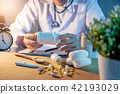 Male doctor holding pill bottle in hospital clinic 42193029