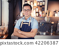 Asian barista standing smiling  in coffee shop 42206387