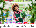 Florist smiling while holding a beautiful potted daisy flower plant 42208940