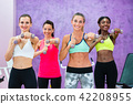 Women exercising with dumbbells during group class in a fitness club 42208955
