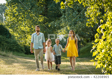 Happy family with two children holding hands during recreational walk 42208965