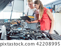 Auto mechanic showing to a customer the engine error codes 42208995