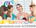 Cheerful woman holding a gift box during a surprise birthday party 42209008