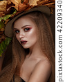 Beautiful blond model in autumn hat : curls, bright makeup, red lips. The beauty face. 42209340