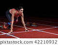 woman sprinter leaving starting blocks on the athletic track. exploding start on stadium with 42210932