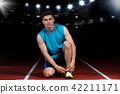 young athletic male sitting on running track and stretching at sports stadium 42211171