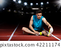 young athletic male sitting on running track and stretching at sports stadium 42211174