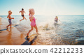Happy kids on vacations at seaside running in the water 42212233