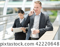 Businessman is using his mobile talk business.  42220648