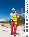 Blue-collar worker carrying a heavy metallic bar during work 42225877