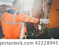 Two refuse collection workers loading garbage into waste truck 42228945