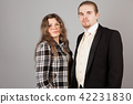 Elegant couple smiling for the camera while embracing. On grey background. 42231830
