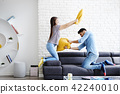 Portrait of Young Couple Playing Pillow Fight 42240010