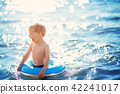 three years old boy playing at the beach with swimming ring 42241017