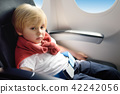 Little boy sitting by aircraft window during the flight 42242056
