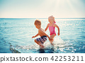 Boy and girl playing on the beach 42253211