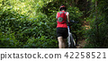 Cyclist carry a mountain bike in the forest 42258521