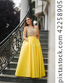 Lady in yellow erening dress stand on stairs 42258905