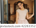 Stylish girl in dress stand in hotel hall. Girl smile to camera 42263352