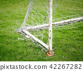 Football goal with old football net in the field.  42267282